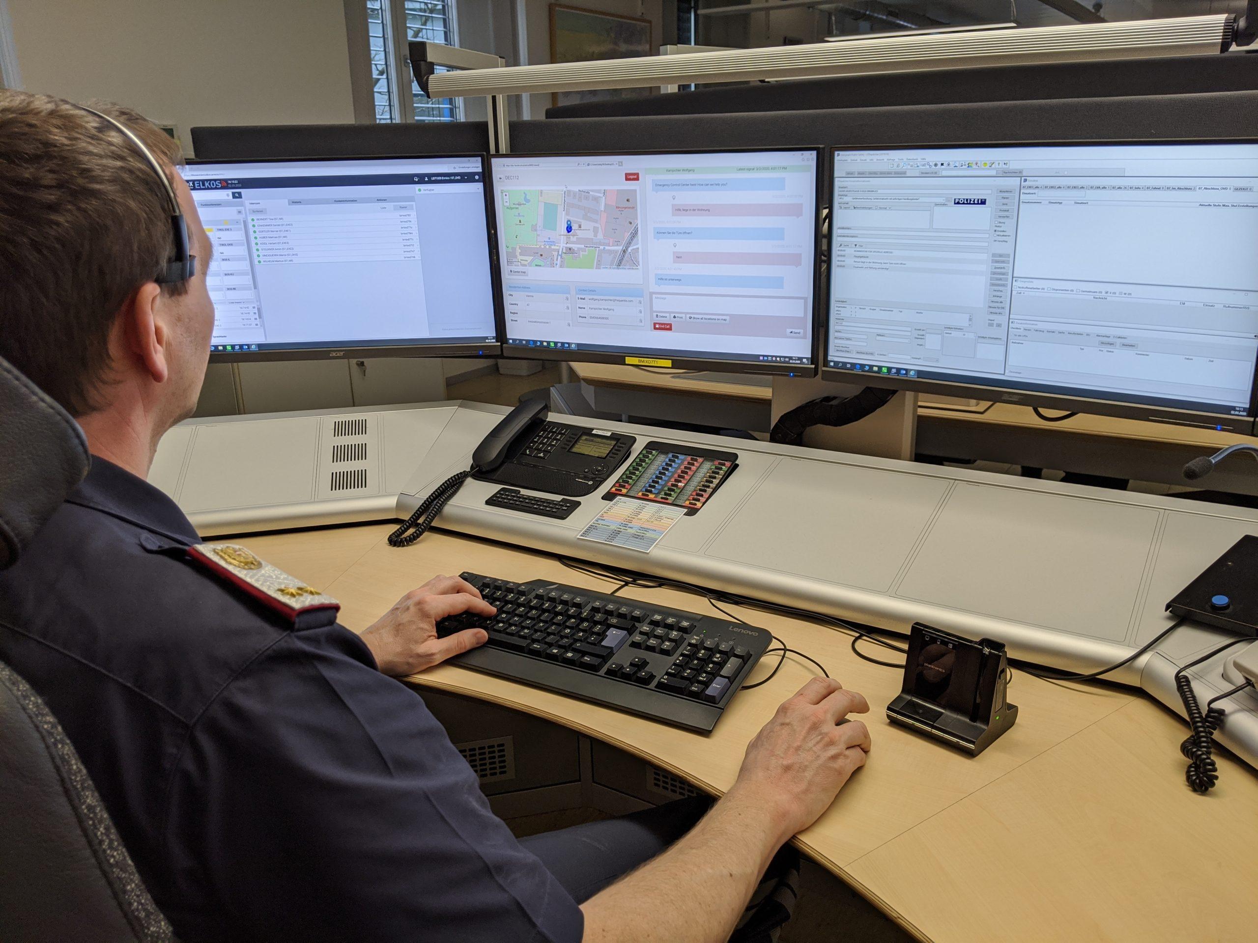 Mitarbeiter der Landespolizeizentrale Tirol sitzt vor 3 Kontrollbildschirmen. Auf einem davon läuft der DEC112 Viewer.